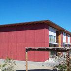 Fassade der Kindertagesstätten aus rot lasierten Dreischichtplatten